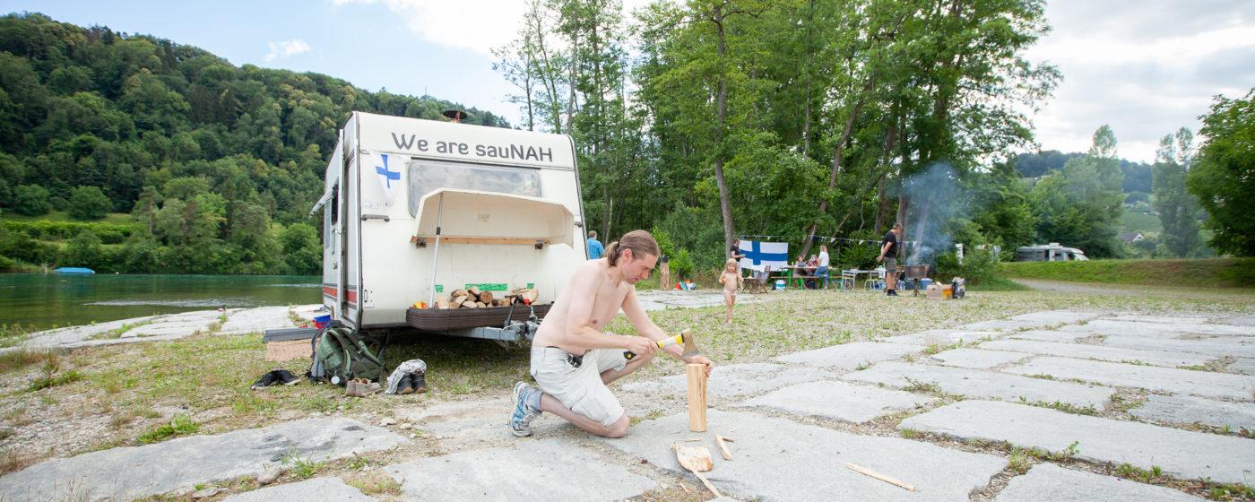 SVFF Gruppe Zürich Mittsommerfest am Rhein mit Sauna. Mikael Lindholm vorbereitet Holz für die Sauna.